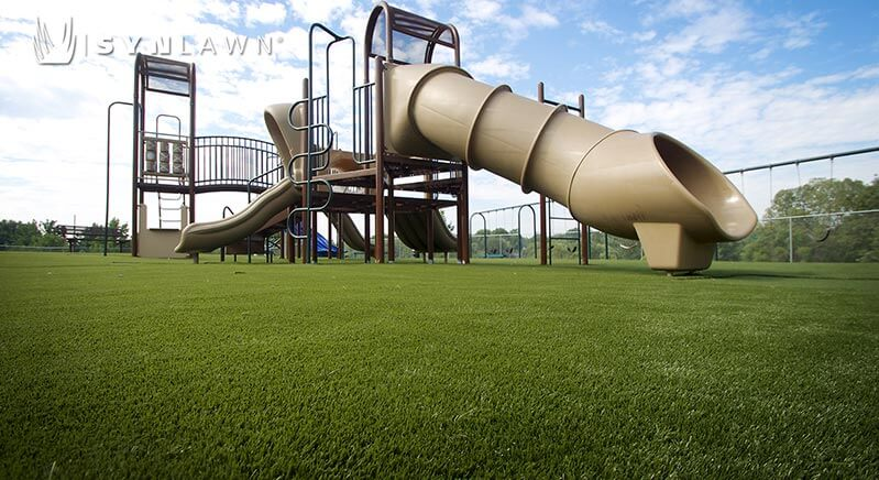 Low angle shot of outdoor playground equipment in tan tones and green playground turf