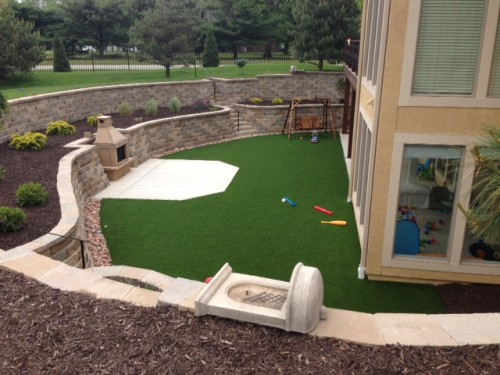 Kansas City artificial turf backyard surrounded by stone retaining walls