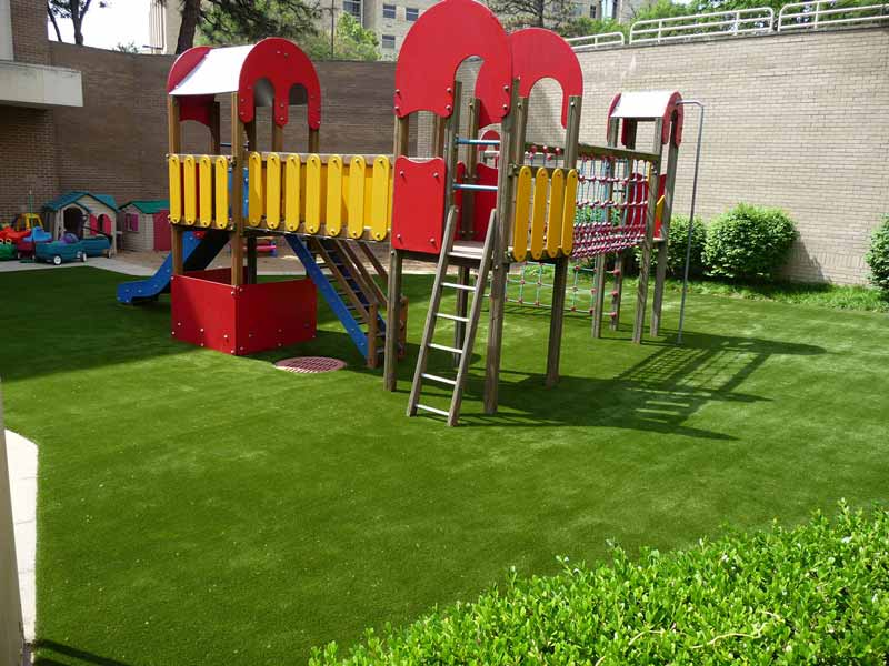Colorful playground equipment atop beautiful green synthetic grass at University of Kansas