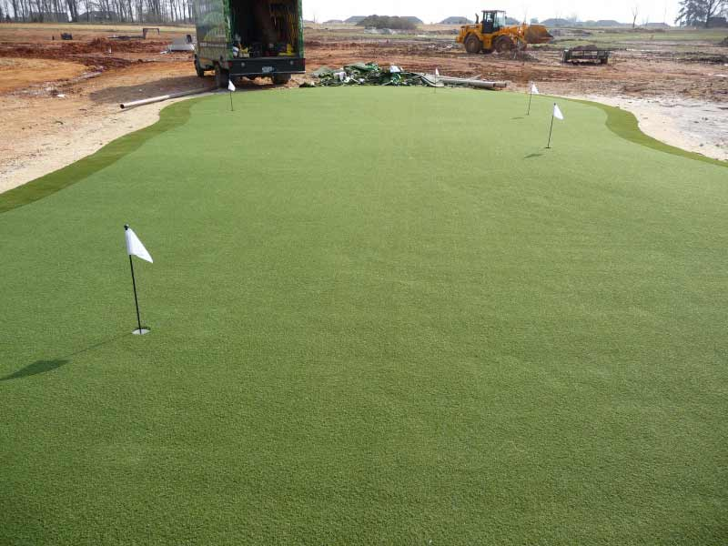 Synthetic putting green finished among large unfinished landscaping project