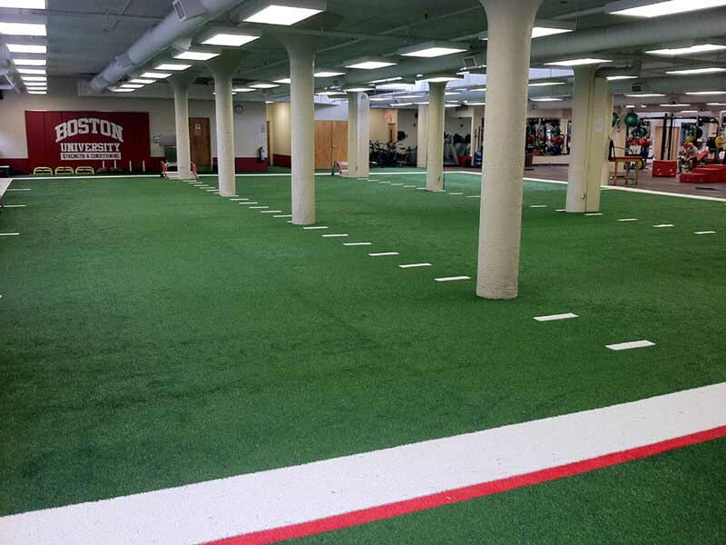 Indoor agility training turf at Boston University with line markers and BU colors