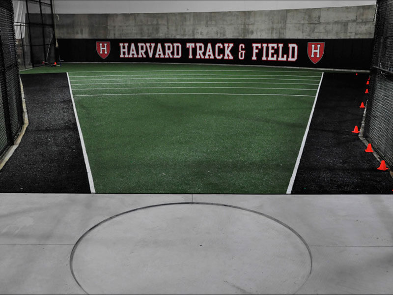 Black and green sport turf inside Harvard Track and Field training facility with orange cones