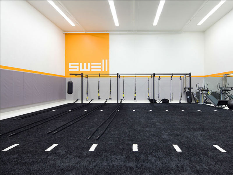 Swell indoor gym with black sports turf and resistance cords rack