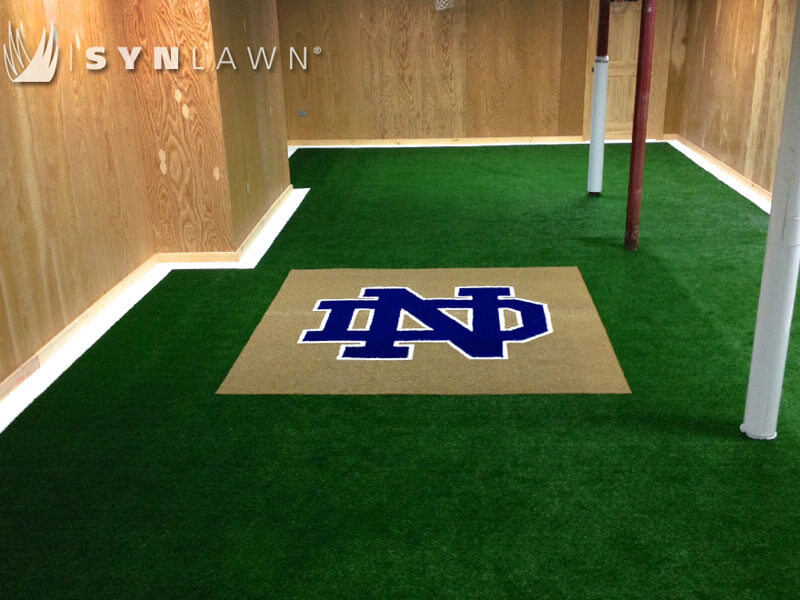 Norte Dame Prepartory logo in blue and white turf surrounded by green turf