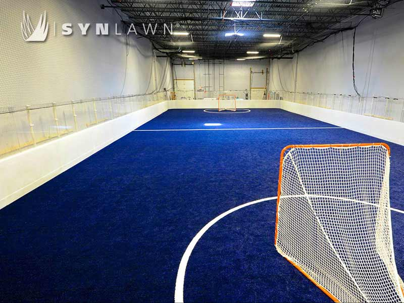 Blue field turf for indoor soccer or roller hockey room with white walls and exposed rafters