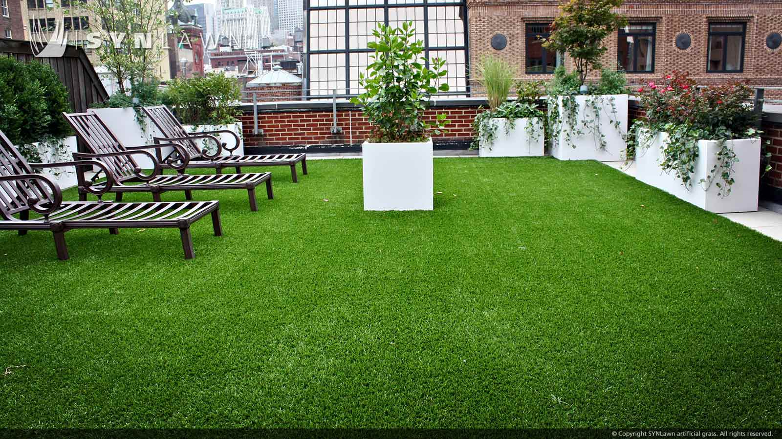 Rooftop artificial grass surrounded by large white planters in downtown Kansas City