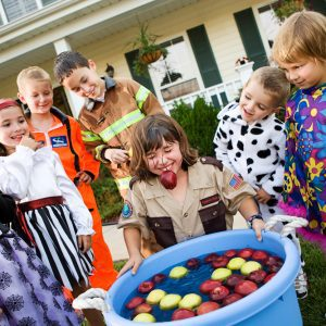 Kid laughs with apple stem in mouth after bobbing for apples with kids nearby in Halloween costumes