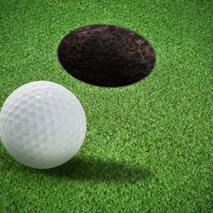 Close-up view of a golf ball near a putting hole on short artificial putting turf
