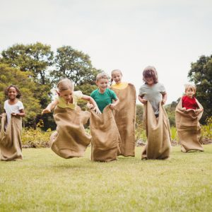 Kids run in burlap sacks across an artificial turf lawn with trees in the background