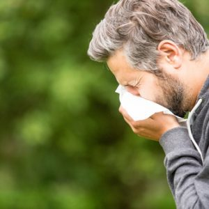 Man outside sneezing into tissue