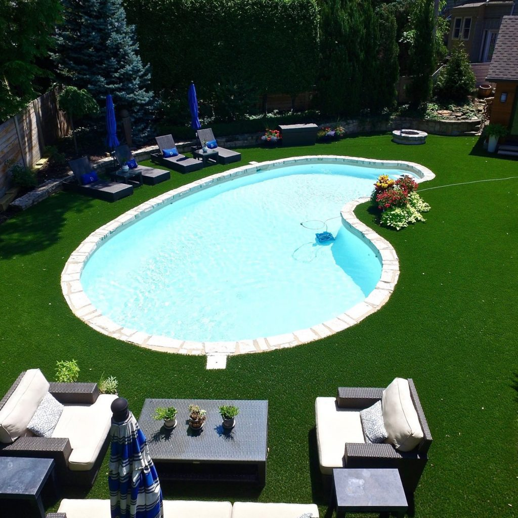 Artificial grass backyard with a pool and patio set.