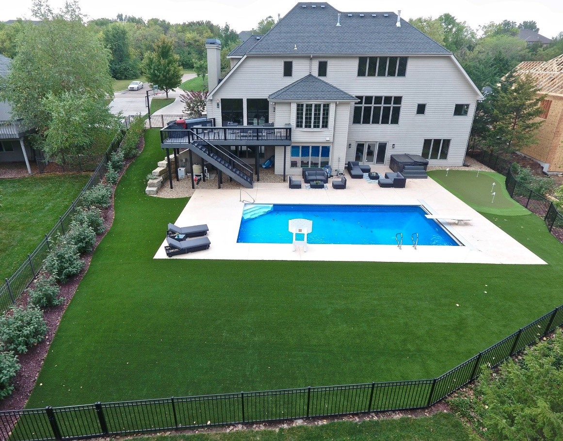 The back of a large house with an artificial grass lawn and pool.