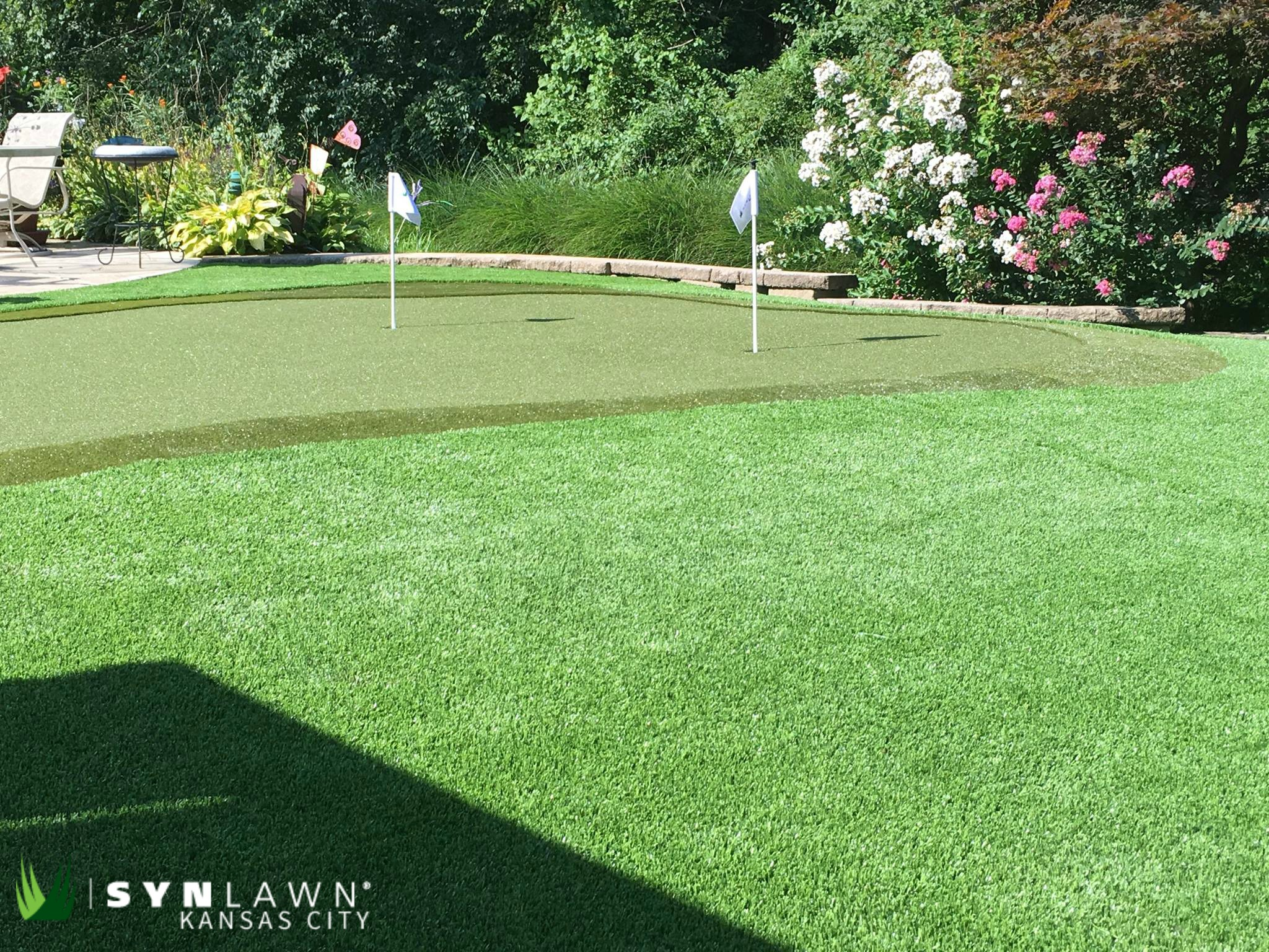 A wide-shot of a synthetic grass putting green with blooming flowers in the background.