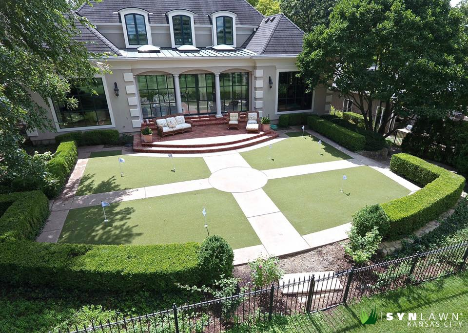 A Kansas City backyard with a synthetic grass lawn and a brick porch with seating.